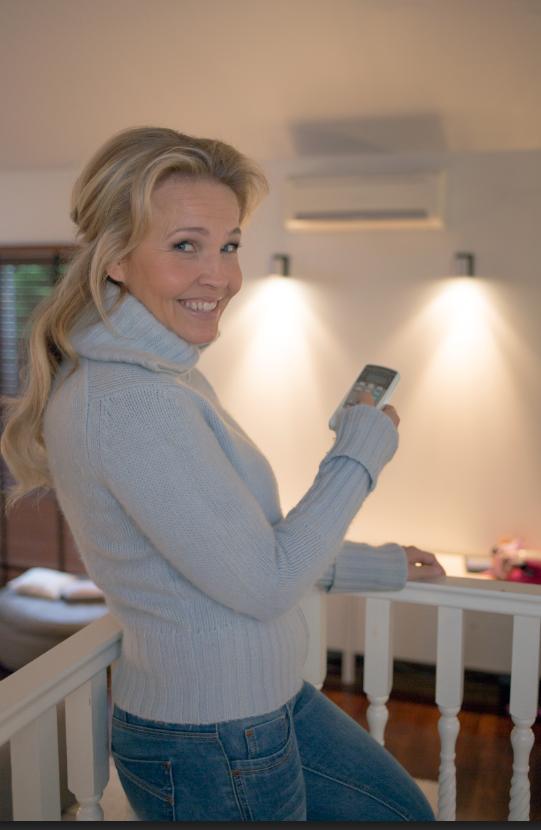 Vattenfallin Vuoden energiaperhekilpailuun osallistunut laulaja Marita Taavitsainen ja ilmalämpöpumppu, joka on auttanut alentamaan lämmityskustannuksia.